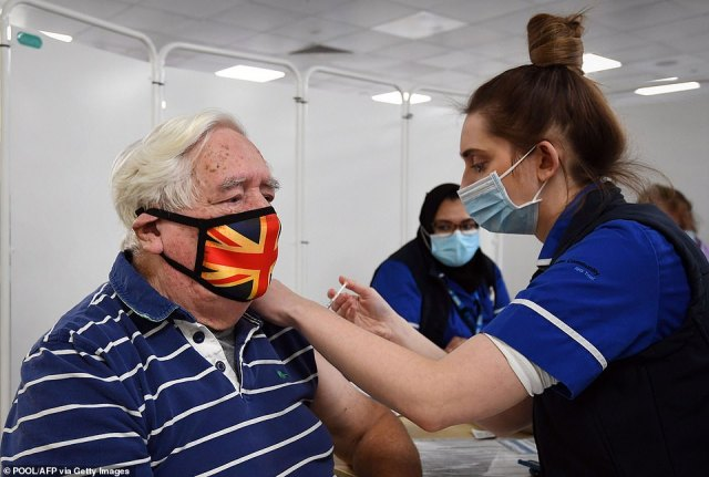 Robert Williams, 84, receives an injection of the Oxford/AstraZeneca Covid-19 vaccine at a mass vaccination centre at Epsom Downs Racecourse