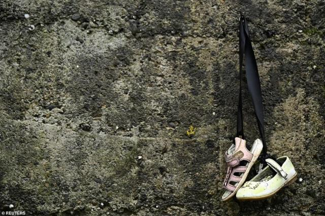 Baby shoes hang yesterday from a wall at the Tuam graveyard, where the bodies of 796 babies were uncovered at the site of a former Catholic home for unmarried mothers and their children