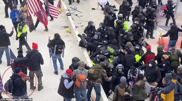 A wider grab from the video shows a man walking up to the group of cops with a fire extinguisher in hand