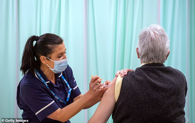 A patient receives an injection of a Covid-19 vaccine at the NHS vaccine centre that has been set up at Robertson House on January 11, 2021 in Stevenage, England