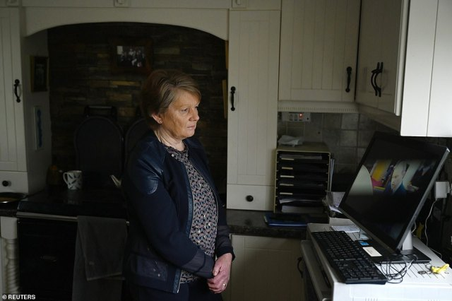 Historian Catherine Corless watches Taoiseach Micheal Martin speaking during a Government webinar meeting for survivors and supporters of Church-run mother and baby homes where he outlines the first look at the report by the Commission of Investigation into the institutions before it is formally published, in Tuam, Ireland, January 12, 2021