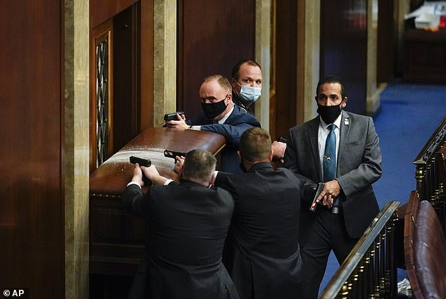 Capitol Police with guns drawn stand near a barricaded door as rioters try to break into the House chamber