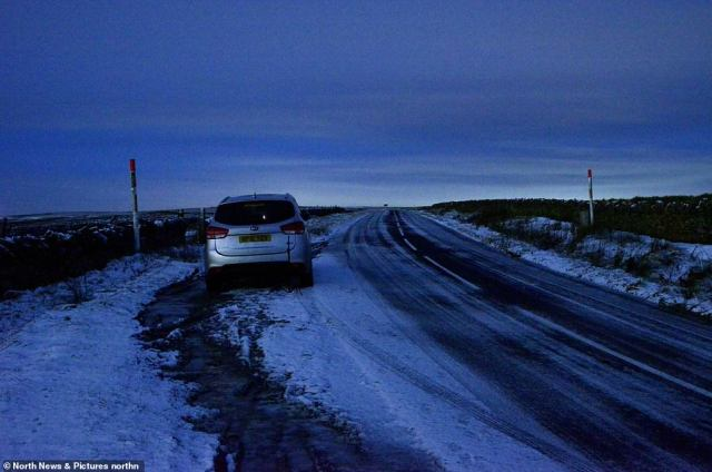 A car parked on the roadside at Allendale in Northumberland this morning as heavy snow is forecast later today