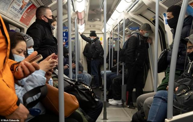 Passengers stand and sit as they travel on the Jubilee line through London on their commute this morning