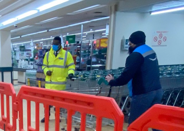 A security guard on the door at Morrisons in Leeds watches customers arrive today to ensure they are wearing masks