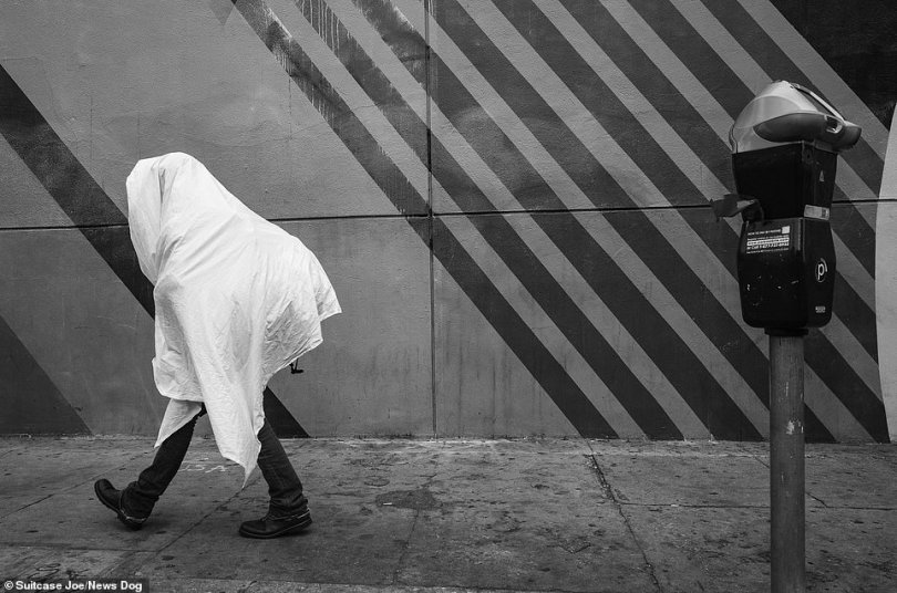 A person with a duvet thrown over them walks the streets of Skid Row.Suitcase Joe is an activist and advocate for the rights of all unhoused individuals. He co-founded the Suitcase Joe Foundation to serve the people of Skid Row with day to day needs and to provide support services for getting into long term housing