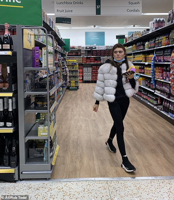 A shopper at a Morrisons in Thamesmead, South East London, brought along her face mask yesterday but failed to utilise it correctly