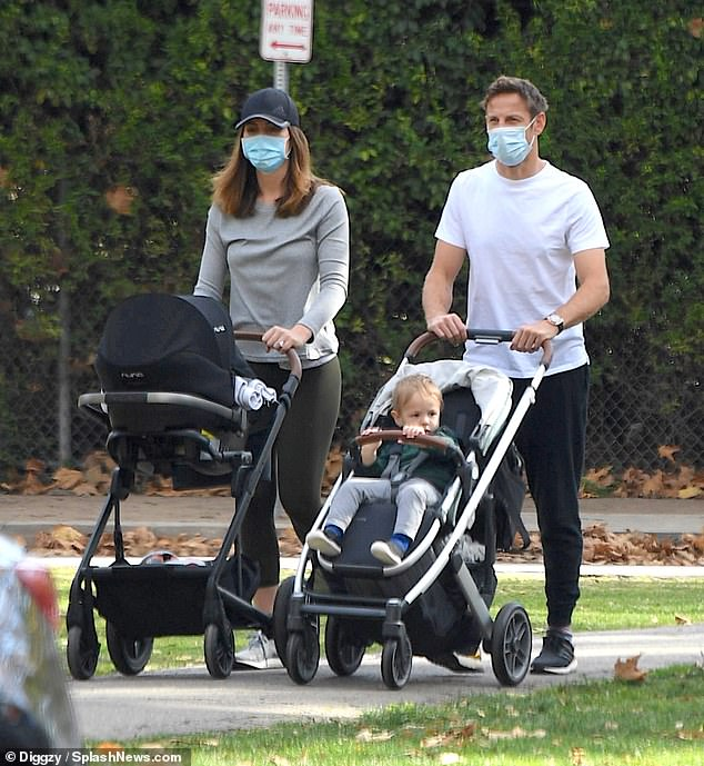 Affectionate dad: Jenson Button looked to be settling into life as a father of two as the family headed for a walk in Beverly Hills on Wednesday