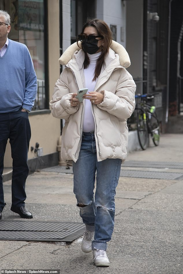 Glam Simple: During her walk she kept her classic maternity style in a pure white turtleneck tucked into loose denim jeans with rips at the knees