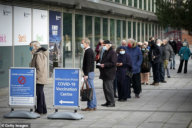 People queue outside the mass NHS Covid-19 vaccine centre that has been set up at the Millennium Point centre in Birmingham