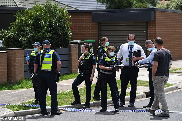 Police in face masks gather in a group outside a house in Tullamarine, after four people were found dead