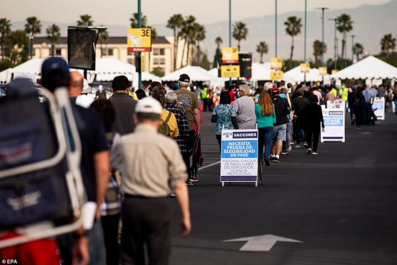 A view of a long line of people waiting to get vaccinated at Disneyland in Anaheim, California on Wednesday above