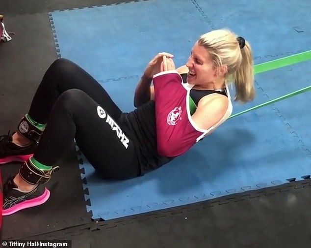 The secret behind those abs: The mother-of-one was also seen gritting her teeth as she worked on her core with another resistance band