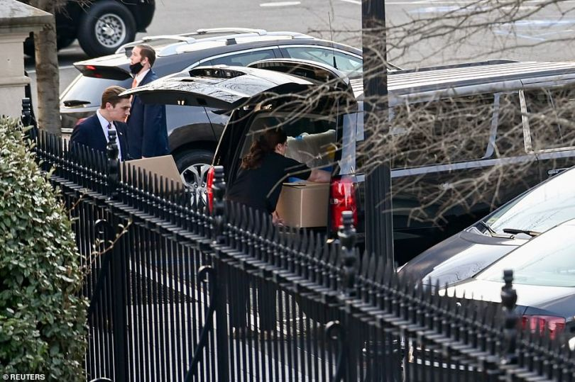 People load boxes and other items from the West Wing of the White House into a car on Wednesday