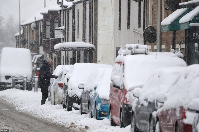 A man brushes snow off a car in Braco near Dunblane this morning as parts of Scotland are hit by blizzards