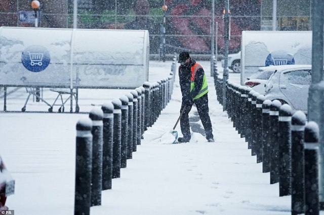 A member of staff from Tesco Extra shovels snow outside the store in Hexham, Northumberland, this morning