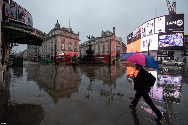 A man with an umbrella walks through a near empty Piccadilly Circus in London this morning