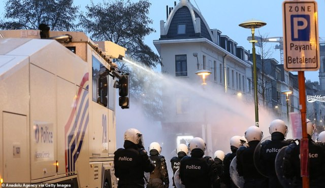 Police officers advance down a street in Brussels as a water cannon is uses to subdue protesters demonstrating following the death of23-year-old Ibrahima Barrie