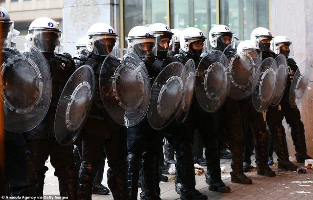 A line of police officers stand guardas demonstrators gather around 'Gare du Nord' during a demonstration after the death of 23-year-old Ibrahima Barrie at the police station