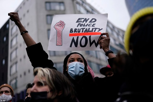 A woman wearing a face mask holds a sign that says 'End police brutality now' following the death of23-year-old Ibrahima Barrie at the police station