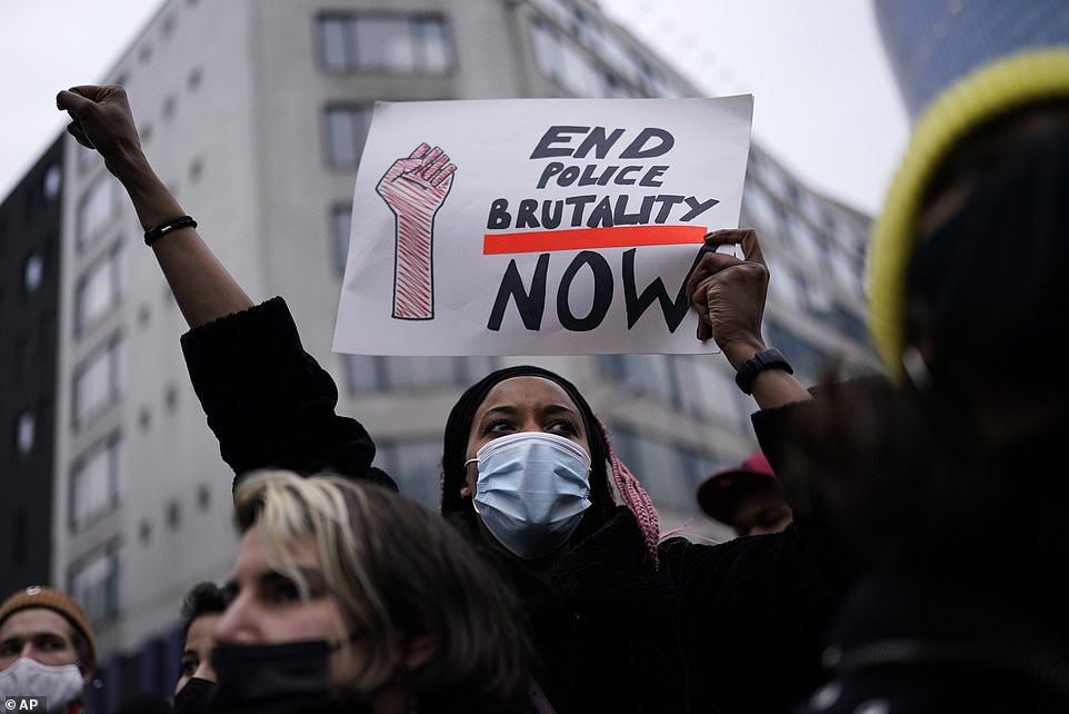 A woman wearing a face mask holds a sign that says 'End police brutality now' following the death of 23-year-old Ibrahima Barrie at the police station