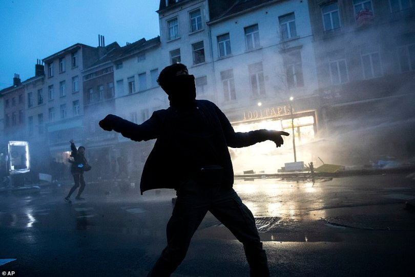 A protester throws stones toward police officers in Brussels on Wednesday as protesters clash with police following the death of a 23-year-old black man in police custody on Saturday