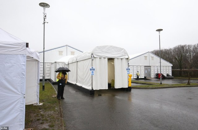 Security staff at the overflow mortuary at Breakspear Crematorium in Ruislip, West London, are pictured in the rain today