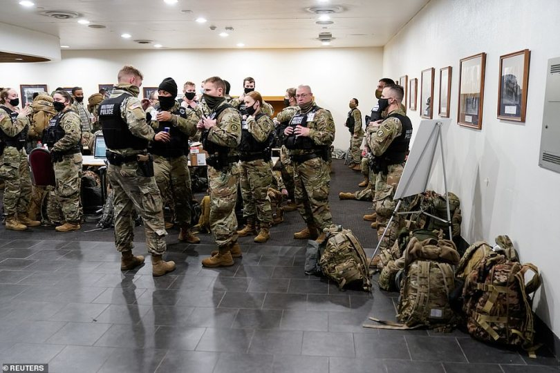 The FBI is warning police chiefs across the US to be on 'high alert' for extremist activity because the deadly siege on the Capitol will be a 'significant driver of violence' during Joe Biden's inauguration. Members of the Military Police are pictured assembling in DC on Thursday morning