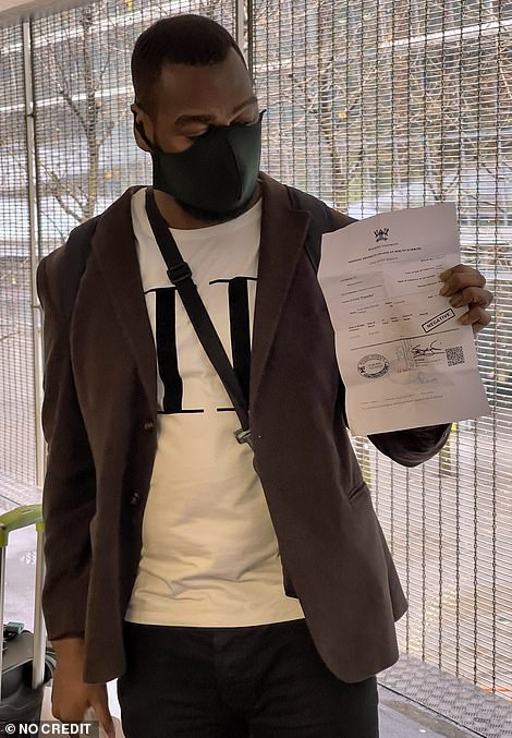 Abdul Yillah (pictured with his negative test certificate) also spoke to MailOnline as they arrived in the UK today at Heathrow
