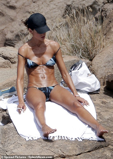 Izabel Goulart flaunts her toned physique in a tie-dye bikini as she tops up her tan in St. Barts