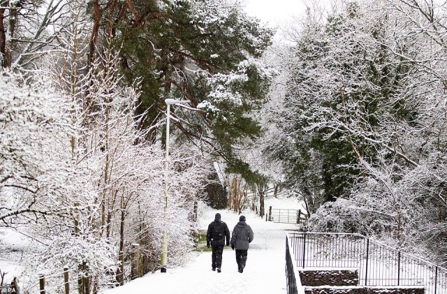 A couple walk through the snow in Auchendinny, Midlothian, today as heavy snow batters parts of the UK