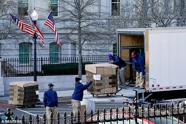 Workers unload pallets of unfolded boxes at the Executive Office Building on the White House ground