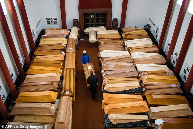 "Employees store coffins, some marked with ""infection risk"" as others have ""corona"" scrawled in chalk, in the mourning hall of the crematorium in Meissen, eastern Germany, on January 13"