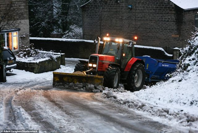 tractor plows and grits a steep road in West Yorkshire after a day of heavy snow