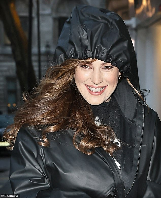 Keeping warm: The presenter, 41, wrapped up in a black PVC raincoat and kept her hood up as she strutted through the capital until she arrived at Global Studios