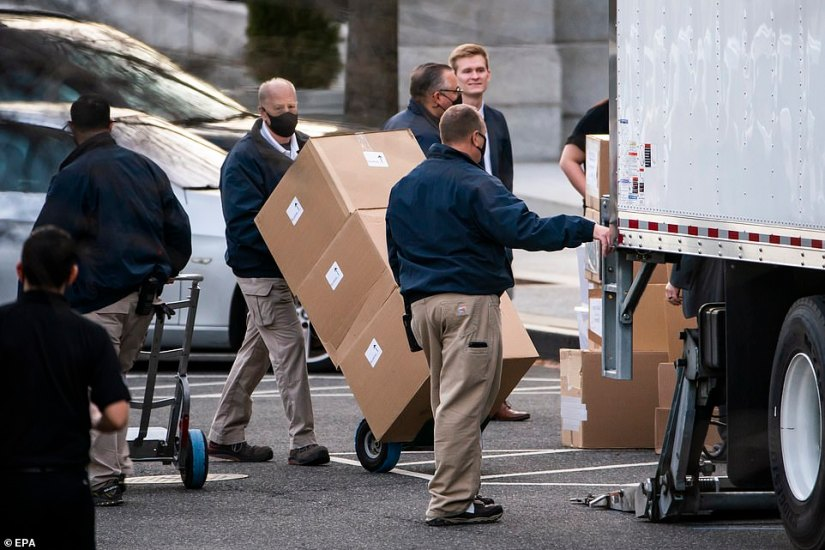 Workers move boxes onto a truck that were stacked on West Executive Avenue between at the White House on Thursday