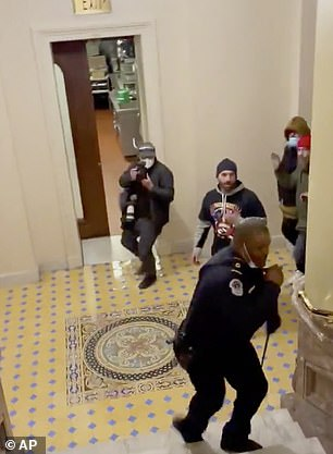 Because the leader of the pack, Doug Jensen - seen wearing a black QAnon shirt - was focused on Goodman, he did not notice the hallway leading to the Senate chambers (above)