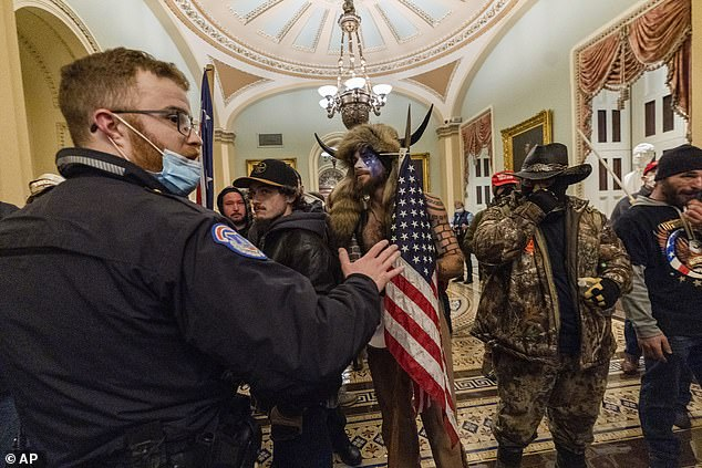 Jacob Chansley of Arizona (in horns), also known as the 'QAnon Shaman', was arrested and charged with two felonies after leaving a note on Pence's desk that read: 'It's only a matter of time, justice is coming'