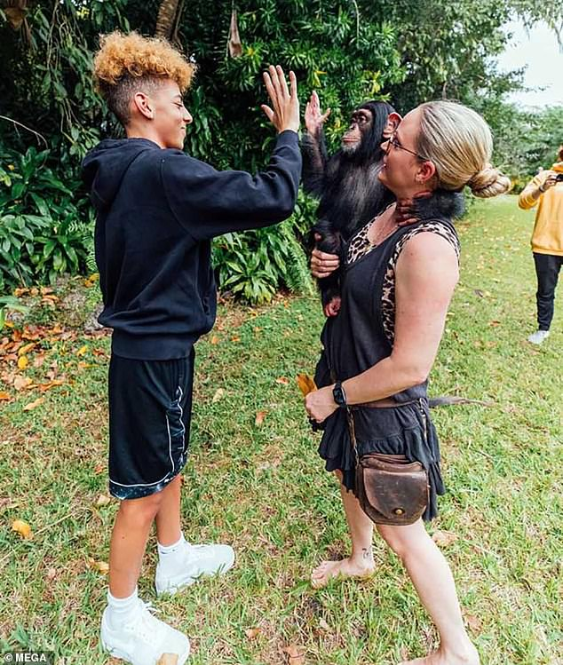 Sweet: The adorable ape showed off its intelligence and sociability by giving Justin a high-five while hanging from one of the guides' arms