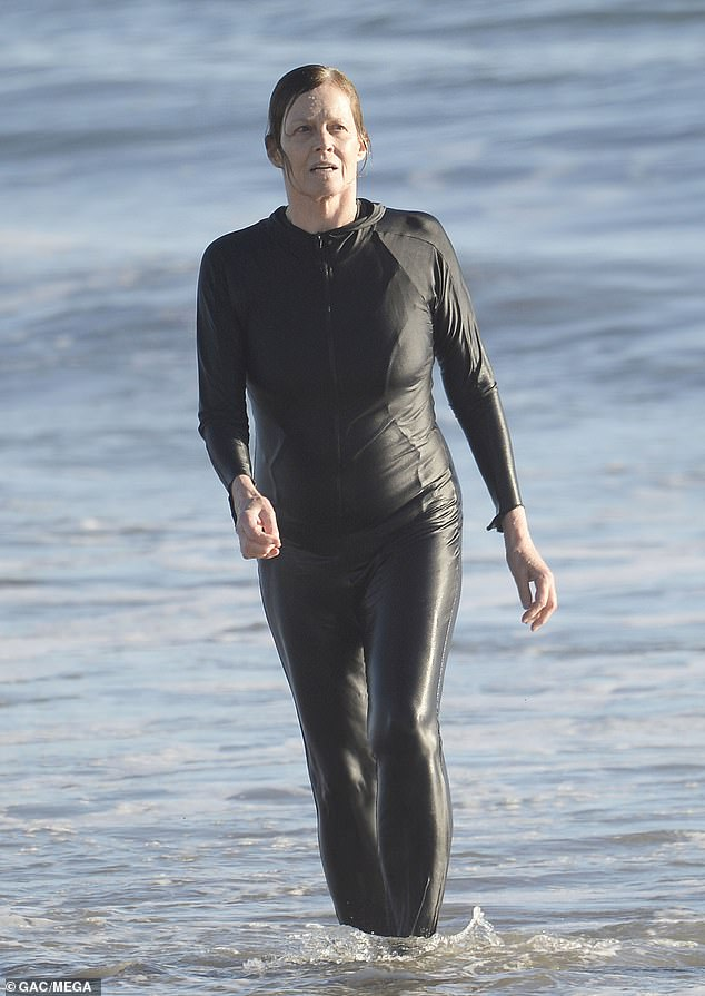 Sigourney Weaver, 71, dons a black wetsuit and holds hands with husband Jim Simpson after a swim