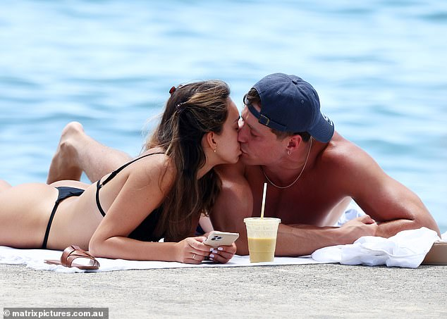 Smooch:The reality star looked to only have eyes for the handsome muscle man, who basked in the sun alongside her