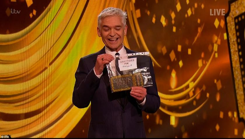 The new normal! Phillip grinned as he held up a 'sanitised for Phillip' golden ticket inside a plastic wallet