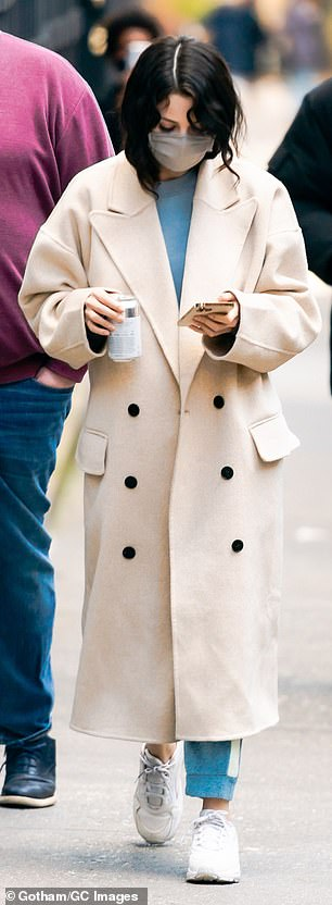 Bundled: Gomez wore an oversized white double-breasted coat over a light-blue sweatshirt, matching sweatpants, and white sneakers