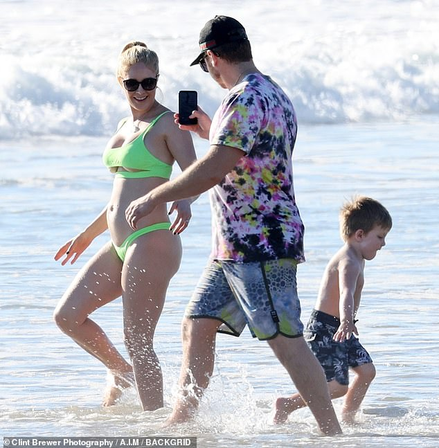 Insta-husband: The crystal enthusiast snapped some photos of Heidi frolicking in the ocean as Gunner got his toes wet