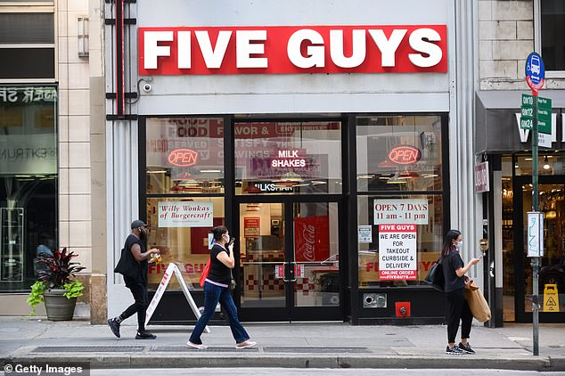 The first eatery will open in the Sydney suburb of Penrith, right next to the Panther's League rugby club on busy Mulgoa Road in the middle of 2021. Pictured: People walk past a Five Guys burger joint in New York City, July 2020