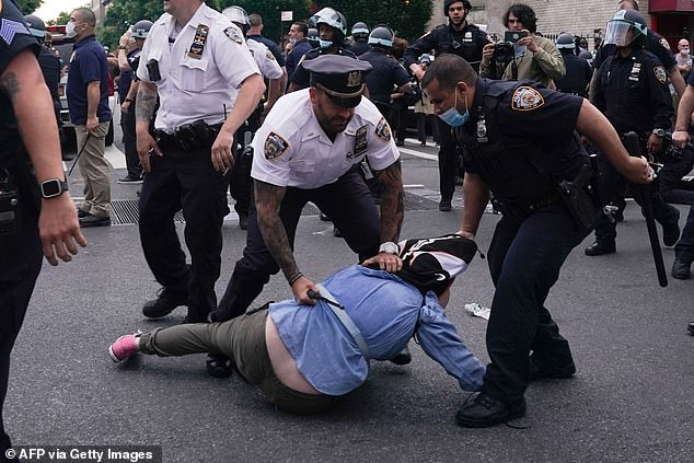 It comes as the culmination following a months-long investigation into the NYPD's actions during racial injustice protests in the Big Apple from May through December (Pictured:NYPD officers arrest protesters during a demonstration against the killing of George Floyd by Minneapolis police on Memorial Day, on May 30)