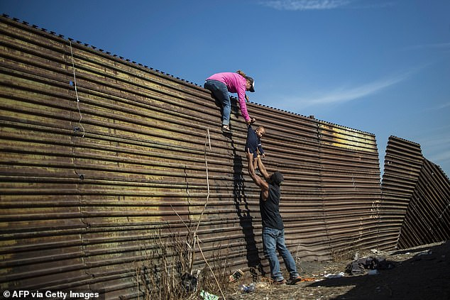 A group of Central American migrants climb the border fence between Mexico and the United States, near El Chaparral border crossing, in Tijuana, Baja California State, Mexico, on November 25, 2018