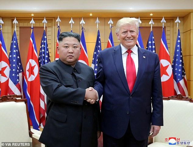 Donald Trump shakes hands with North Korean leader Kim Jong Un