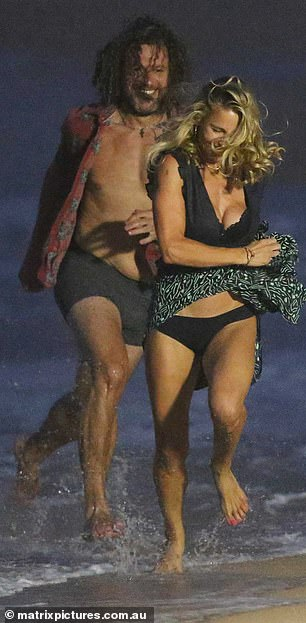Come 'ere! Her co-star wore an open shirt and black briefs as he chased Elsa around the shore