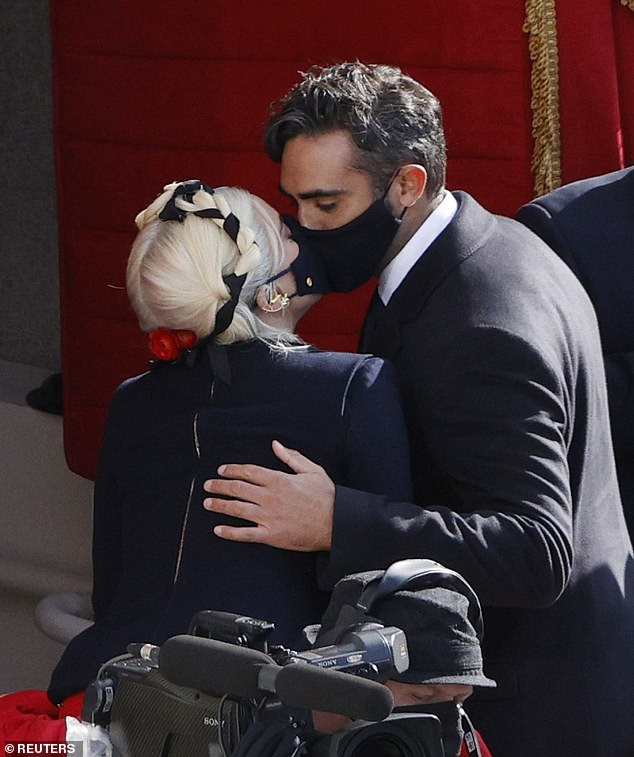 A smooch for his lady love:They were seen in the crowd as he wore a dark suit. And at one point they kissed through their black masks